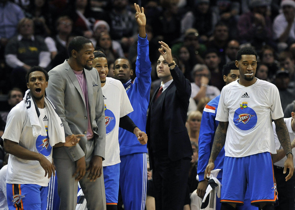 Photo - Oklahoma City Thunder players on the bench celebrate a 3-point basket during the second half of an NBA basketball game against the San Antonio Spurs, Thursday, Dec. 25, 2014, in San Antonio. Oklahoma City won 114-106. (AP Photo/Darren Abate)
