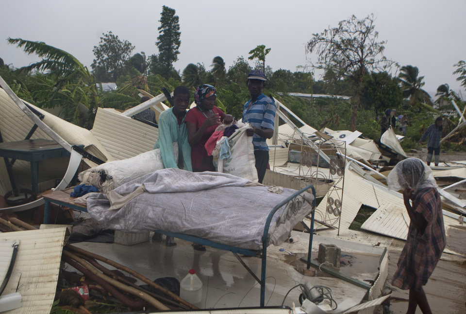 Photo -   A family salvages what is left of their home at a camp set up for people displaced by the 2010 earthquake that was destroyed by Tropical Storm Isaac in Port-au-Prince, Haiti, Saturday Aug. 25, 2012. Tropical Storm Isaac swept across Haiti's southern peninsula early Saturday, dousing a capital city prone to flooding and adding to the misery of a poor nation still trying to recover from the 2010 earthquake. (AP Photo/Dieu Nalio Chery)
