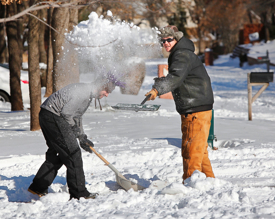 Photo - Friends Colton Fees and Zac Cumpston join forces  Wednesday Feb, 2, 2011, morning to clear a driveway on Coachlight Drive in Edmond. Central Oklahoma residents  began digging out from beneath nearly a foot of snow covering the ground after yesterday's winter snowstorm. Photo by Jim Beckel, The Oklahoman
