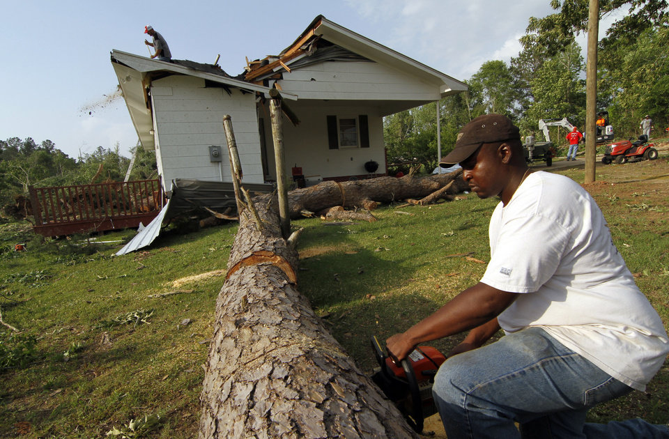 Photo - Undeon Hardy cuts a section of pine that damaged the Longino, Miss., home of John Mullins following a tornado touchdown that caused several deaths nearby Wednesday, April 27, 2011. Several tornadoes hit  in the state resulting in number of deaths. (AP Photo/Rogelio V. Solis)