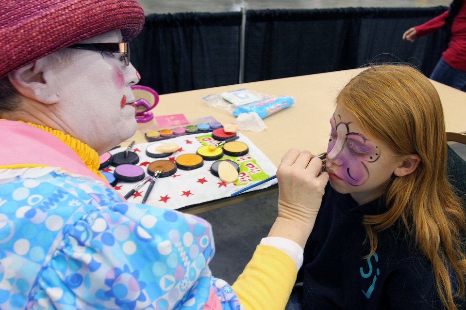 Photo - Flutterbye (Sabrina Evans) paints a butterfly on Aliya Fronko, of Edmond, at the face-painting booth during Opening Night 2012 festivities at the Cox Convention Center. Oklahoman Archives Photo