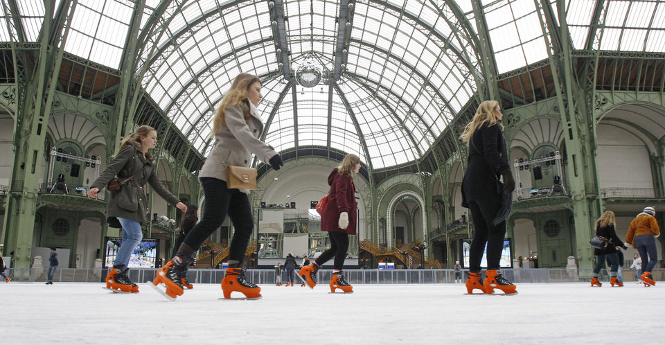 Skaters take advantage of the giant ice rink set up under the famous glass roof of the Grand Palais, in Paris Thursday Dec. 13, 2012. The Grand Palais skating rink is the largest temporary ice rink ever created in France. It will remain open until Jan. 6, 2013.(AP Photo/Remy de la Mauviniere)