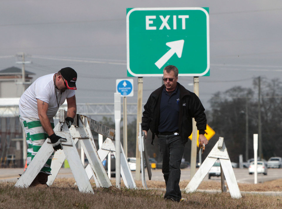 Photo - David Hansen of Gulfport, Miss., police, right, and state trusty Josh Sullivan put barricades out at the I-10 on ramp at U.S. 49 in Gulfport on Monday Jan. 27, 2014 in peparation for expected icy road conditions on Tuesday and Wednesday. (AP Photo/Sun Herald, John Fitzhugh)