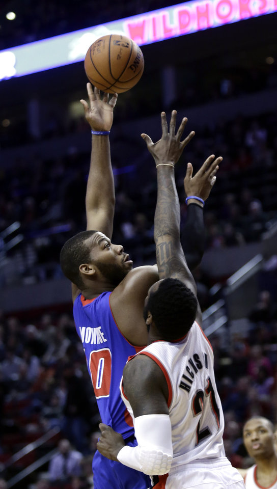 Detroit Pistons center Greg Monroe, left, shoots over Portland Trail Blazers center J.J. Hickson during the first quarter of an NBA basketball game in Portland, Ore., Saturday, March 16, 2013. (AP Photo/Don Ryan)