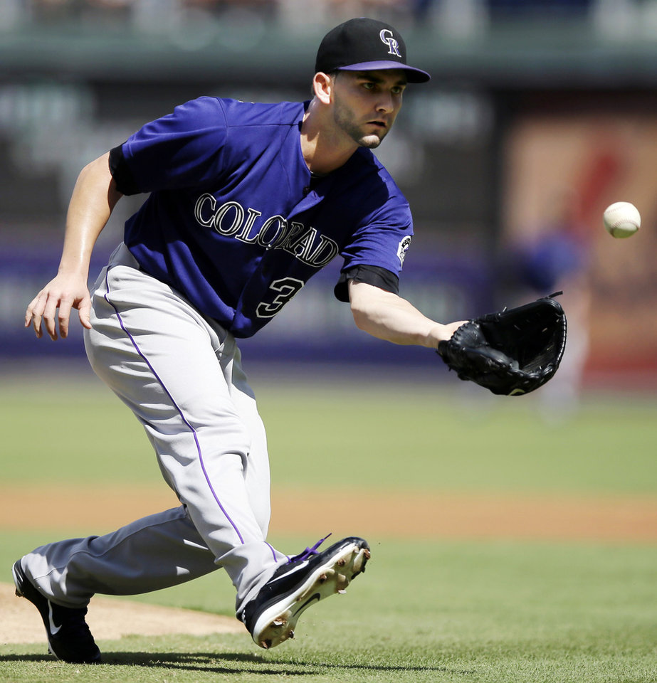 Photo -   Colorado Rockies relief pitcher Tyler Chatwood fields a ground out by Philadelphia Phillies' Chase Utley in the first inning of the first game of a baseball doubleheader, Sunday, Sept. 9, 2012, in Philadelphia. (AP Photo/Matt Slocum)