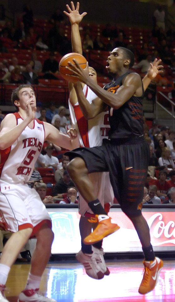 Photo - OKLAHOMA STATE UNIVERSITY, OSU:  Oklahoma State's Terrel Harris, right, scores over Texas Tech's John Roberson (21) and Robert Lewandowski (15) during the first half of an NCAA college basketball game at United Spirit Arena in Lubbock, Texas, Wednesday, Feb. 18, 2009. (AP Photo/Lubbock Avalanche-Journal,Geoffrey McAllister) ORG XMIT: TXLUB102