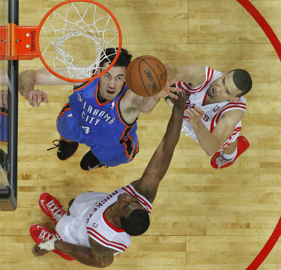 Photo - Oklahoma City's Nick Collison (4) reaches for the ball between Houston's Terrence Jones (6) and Francisco Garcia (32) during Game 3 in the first round of the NBA playoffs between the Oklahoma City Thunder and the Houston Rockets at the Toyota Center in Houston, Texas, Sat., April 27, 2013. Oklahoma City won 104-101. Photo by Bryan Terry, The Oklahoman