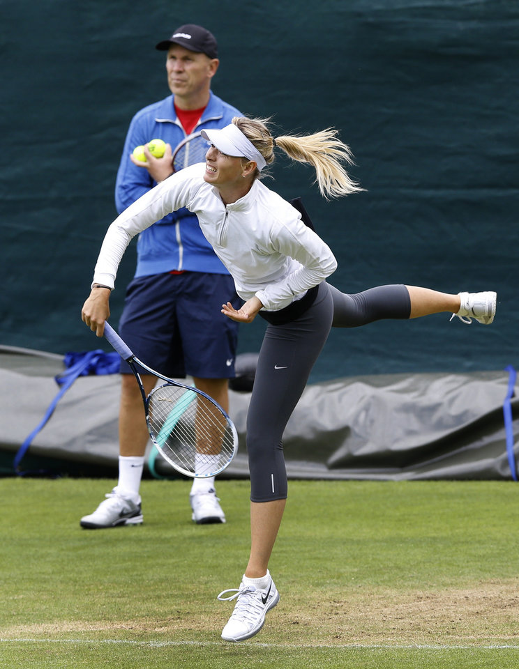 Photo - Maria Sharapova of Russia is watched by a coach during a training session at the Wimbledon tennis championships in London, Sunday, June 23, 2013. The Championships start Monday, with Serena Williams attempting to win the title for the sixth time. (AP Photo/Kirsty Wigglesworth)