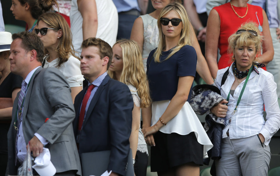 Photo - Maria Sharapova of Russia, second right, waits to leave the players box after watching her boyfriend Grigor Dimitrov of Bulgaria defeated by Novak Djokovic of Serbia in their men's singles semifinal match at the All England Lawn Tennis Championships in Wimbledon, London, Friday, July 4, 2014. (AP Photo/Pavel Golovkin)