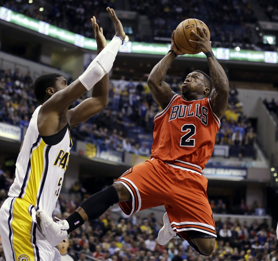 Chicago Bulls guard Nate Robinson, right, puts his foot against Indiana Pacers center Roy Hibbert as he shoots in the first half of an NBA basketball game in Indianapolis, Monday, Feb. 4, 2013. (AP Photo/Michael Conroy)