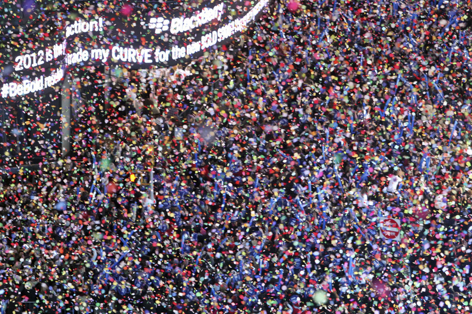 Photo - FILE - In this Dec. 31, 2011 file photo, confetti flies over New York's Times Square as the clock strikes midnight during the New Year's Eve celebration as seen from the balcony of the Marriott Marquis hotel. It's no small task making sure the annual celebration remains safe, but the New York City police use an array of security measures for the event that turns the