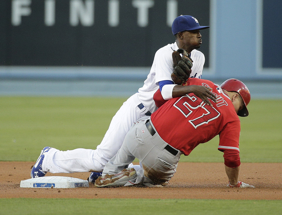 Photo - Los Angeles Dodgers second baseman Dee Gordon, top, watches his throw to first base after forcing out Los Angeles Angels' Mike Trout during the first inning of a baseball game on Tuesday, Aug. 5, 2014, in Los Angeles. Albert Pujols was out at first. (AP Photo/Jae C. Hong)