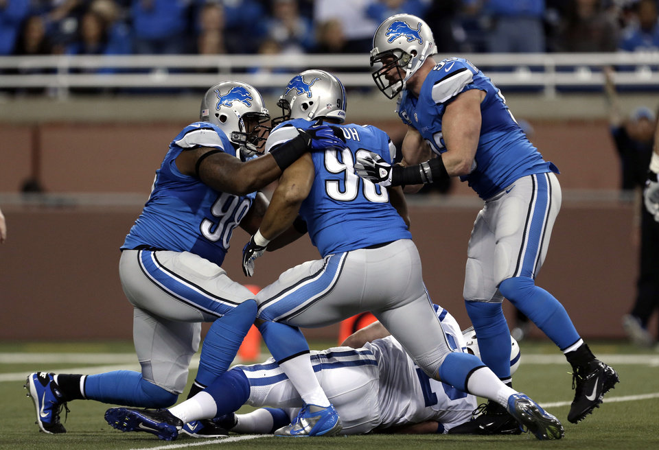 Photo - From left, Detroit Lions defensive tackle Ndamukong Suh (90), Nick Fairley (98) and Kyle Vanden Bosch (93) celebrate after sacking Indianapolis Colts quarterback Andrew Luck, bottom, in the first quarter of an NFL football game in Detroit, Sunday, Nov. 2, 2012. (AP Photo/Paul Sancya)