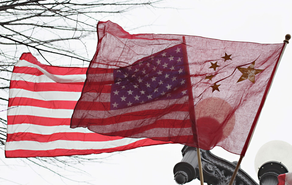 Photo - FILE - In this Jan. 17, 2011 file photo, American and Chinese flags fly along Pennsylvania Avenue in front of the White House in Washington. The Justice Department's indictment last week of five Chinese military officials charged them with trying to pilfer confidential information from American companies. But even some of the alleged U.S. corporate victims of the hackers have little incentive to cheer any trade rupture with China. (AP Photo/Carolyn Kaster, File)