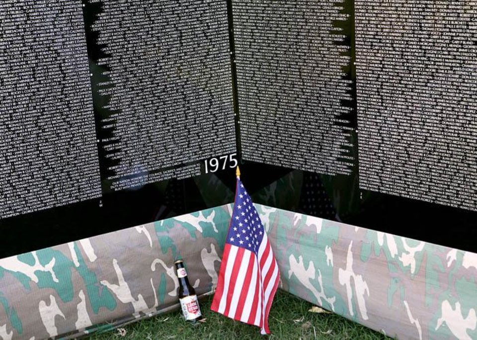 A bottle of beer left near a flag at The Moving Wall exhibit, a replica of Vietnam Veterans Memorial in Washington DC, at  Woodland Park in Shawnee , Okla., on Sunday, August 23, 2009. By John Clanton, The Oklahoman ORG XMIT: KOD
