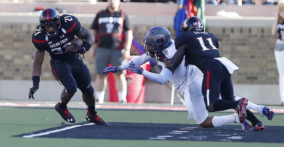 Photo - Texas Tech's DeAndre Washington (21) runs the ball as Jakeem Grant (11) blocks Central Arkansas' Bobby Watkins during an NCAA college football game in Lubbock, Texas, Saturday, Aug. 30, 2014. (AP Photo/Lubbock Avalanche-Journal, Tori Eichberger) ALL LOCAL TELEVISION OUT