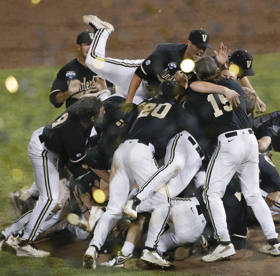 Photo - Vanderbilt players celebrate after Vanderbilt defeated Virginia 3-2 in the deciding game of the best-of-three NCAA baseball College World Series finals in Omaha, Neb., Wednesday, June 25, 2014. (AP Photo/Nati Harnik)