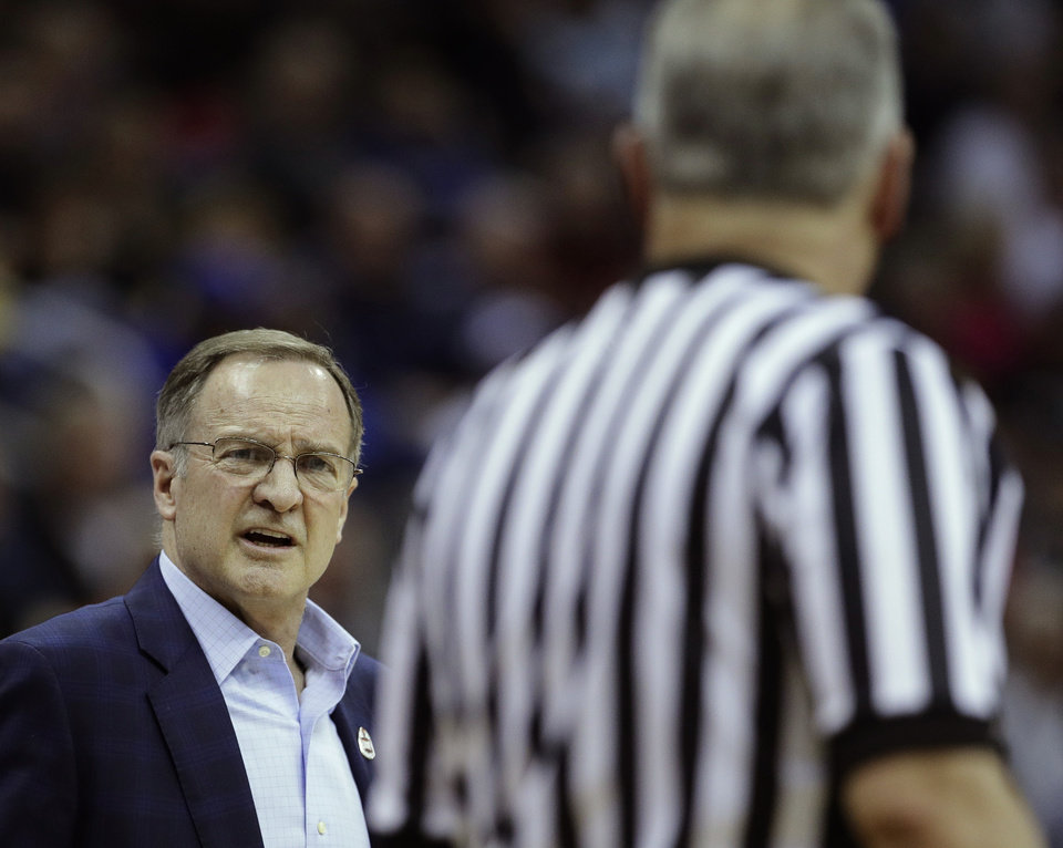 Photo - Oklahoma coach Lon Kruger talks to an official during the first half of the team's NCAA college basketball game against Oklahoma in the Big 12 men's tournament Wednesday, March 13, 2019, in Kansas City, Mo. (AP Photo/Charlie Riedel)