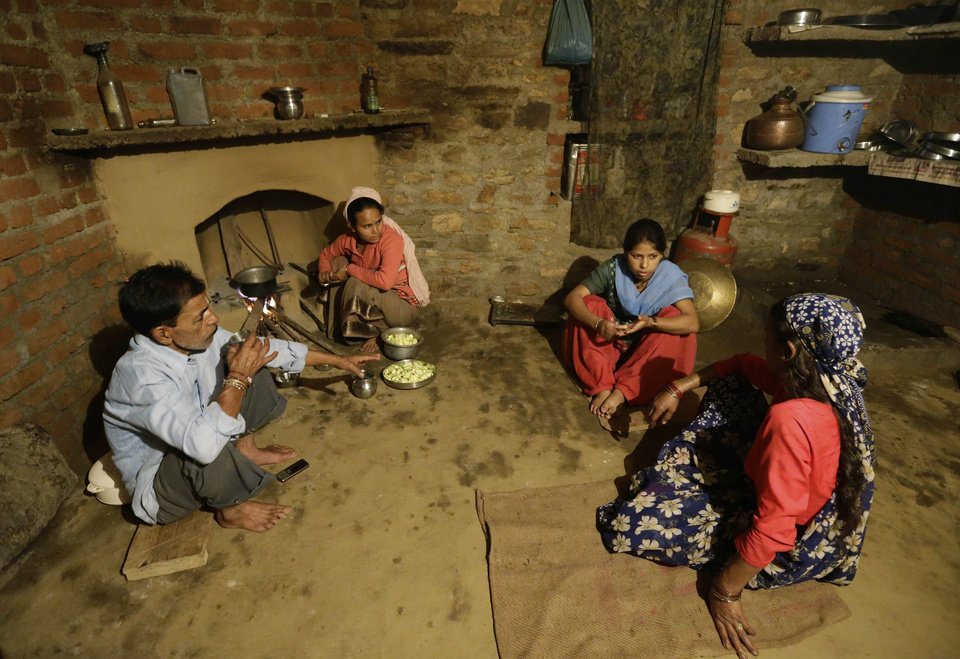 Photo -   In this Aug. 24, 2012 photo, Shoba Bisht, second right, sits with her family at the kitchen she has helped build with money earned from working at B2R, in Simayal, India. Before B2R arrived in Simayal, local women had little option but to marry right out of school, and educated young men had to travel far to seek respectable jobs. (AP Photo/Saurabh Das)