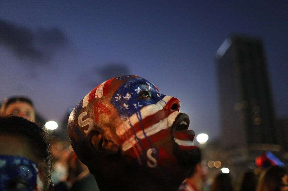 Photo - A U.S. soccer fan watches his team's World Cup round of 16 match against Belgium on a live telecast inside the FIFA Fan Fest area on Copacabana beach in Rio de Janeiro, Brazil, Tuesday, July 1, 2014. (AP Photo/Leo Correa)
