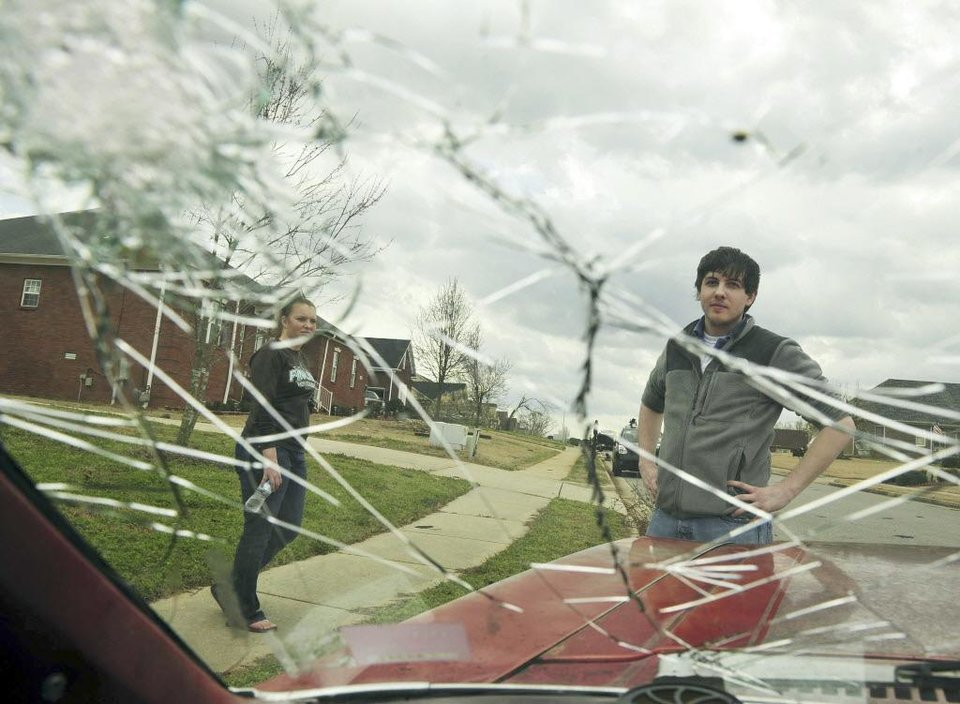 Joseph Bullock looks through the broken glass of a  car after it was hit with debris on Jacob's Landing Drive after a tornado hit in the northern part of Madison county Friday, March 2, 2012 in Meridianville, Ala. Reported tornadoes destroyed several houses and hit a maximum security prison in northern Alabama as bad weather threatened more twisters across the region Friday, two days after a storm system killed 13 people in the Midwest and South.  (AP Photo/The Huntsville Times, Eric Schultz) ORG XMIT: ALHUT125