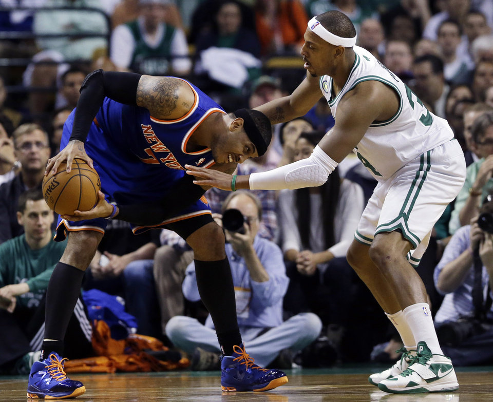 Photo - New York Knicks forward Carmelo Anthony, left, makes a move against the defense of Boston Celtics forward Paul Pierce during the first half in Game 4 of a first-round NBA basketball playoff series in Boston, Sunday, April 28, 2013. (AP Photo/Elise Amendola)