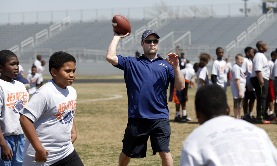 Photo - Denver Broncos' Wes Welker throws a ball during the Wes Welker pro camp at Douglass High School in  Oklahoma City., Saturday, April 05, 2014. Photo by Sarah Phipps, The Oklahoman