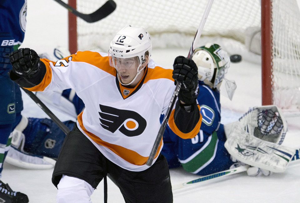 Philadelphia Flyers left wing Michael Raffl (12) celebrates teammate Mark Streit\'s goal past Vancouver Canucks goalie Eddie Lack (31) during the first period of an NHL hockey game in Vancouver, British Columbia, Monday, Dec. 30, 2013. (AP Photo/The Canadian Press, Jonathan Hayward)