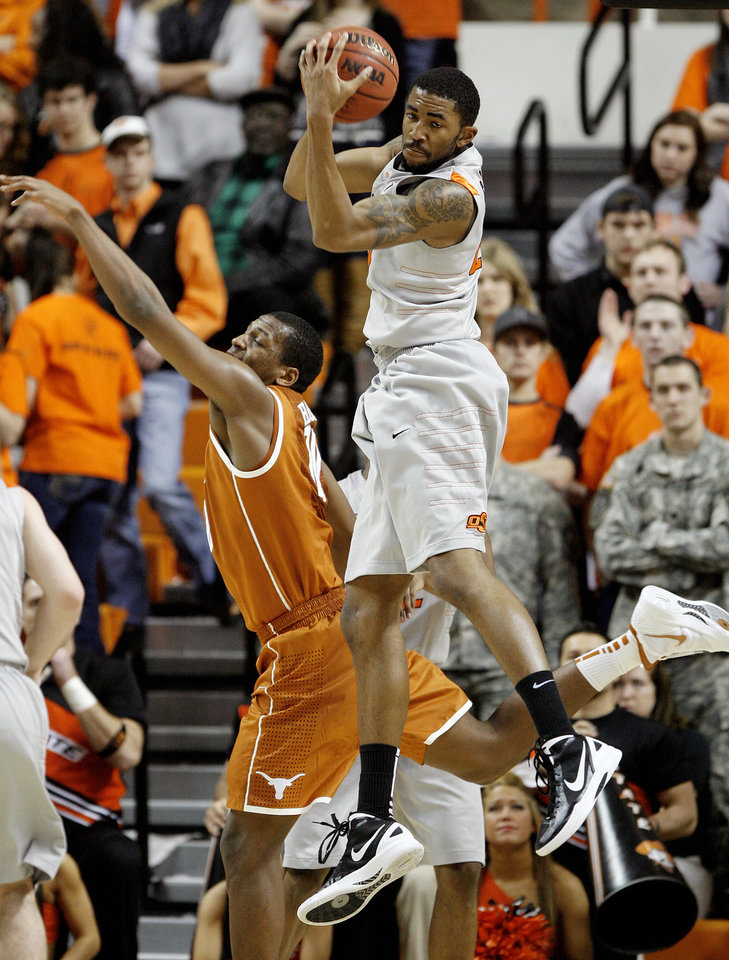 Photo - Oklahoma State's Michael Cobbins (20) grabs a rebound over Texas' Jonathan Holmes (10) during an NCAA college basketball game between Oklahoma State University (OSU) and the University of Texas (UT) at Gallagher-Iba Arena in Stillwater, Okla., Saturday, Feb. 18, 2012. Oklahoma State won 90-78. Photo by Bryan Terry, The Oklahoman