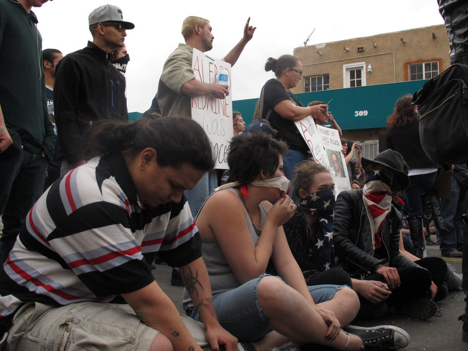 Photo - Protesters sit in downtown Albuquerque, N.M. during a rally Sunday March 30, 2014,  against recent police shootings. Hundreds of protesters marched past riot police in Albuquerque on Sunday, days after a YouTube video emerged threatening retaliation for a recent deadly police shooting. The video, which bore the logo of the computer hacking collective Anonymous, warned of a cyber attack on city websites and called for the protest march. (AP Photo/Russell Contreras)
