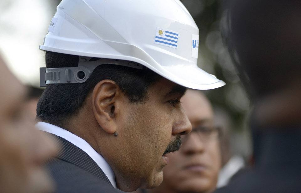 Photo - Venezuela's President Nicolas Maduro wears a helmet decorated with an Uruguayan flag as he visits the Urutransfor factory, which produces transformers, in Montevideo, Uruguay, Tuesday, May 7, 2013. Maduro is on a one-day official visit to Uruguay. (AP Photo/Matilde Campodonico)