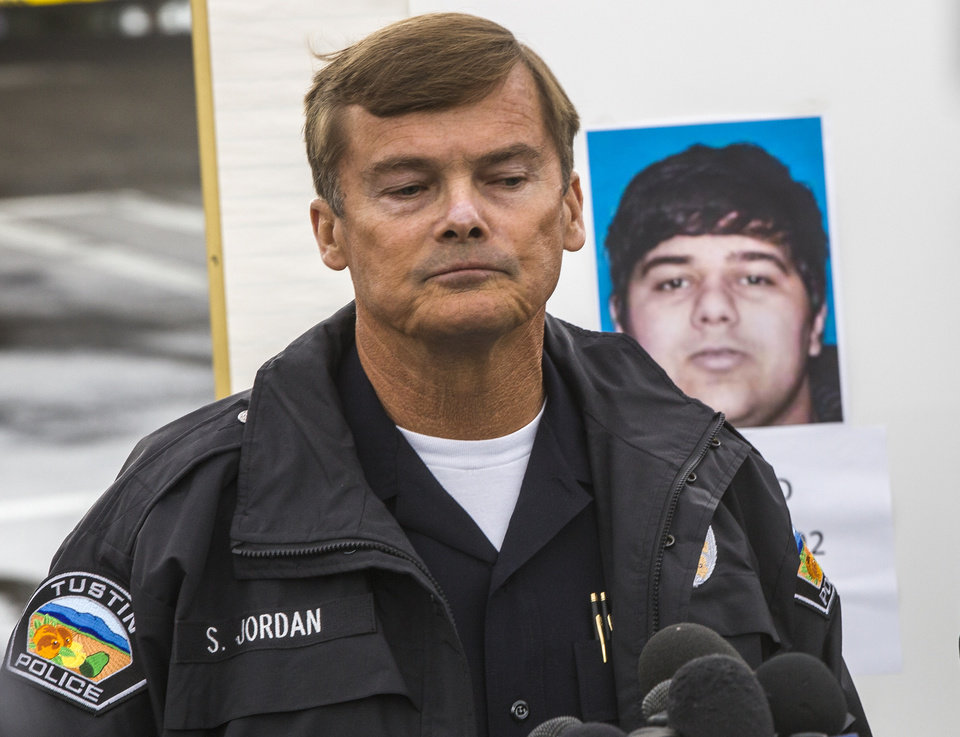 Photo - Tustin Police Chief Scott Jordan takes questions about the gunman, Ali Syed, a suspect in a series of shootings during a news conference in Tustin, Calif., Tuesday, Feb. 19, 2013. In less than an hour, Syed, an unemployed part-time student, shot and killed a woman in her home and two commuters during carjackings early Tuesday, shot up vehicles on a Southern California freeway and committed suicide as police closed in on him, authorities said. (AP Photo/Damian Dovarganes)
