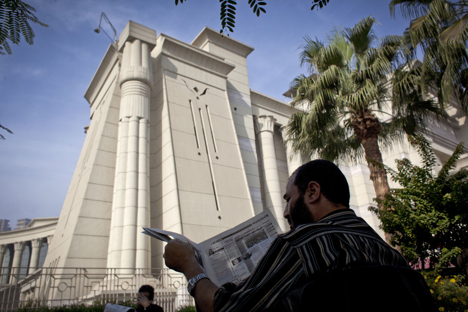 Photo - A supporter of Egyptian President Mohammed Morsi reads a newspaper during a protest in front of Egypt's top court, in Cairo, Egypt, Monday, Dec. 3, 2012. The Egyptian president's top legal adviser says the country's election commission has begun preparations for the referendum on Dec. 15 on a highly contentious draft constitution. (AP Photo/Nasser Nasser)