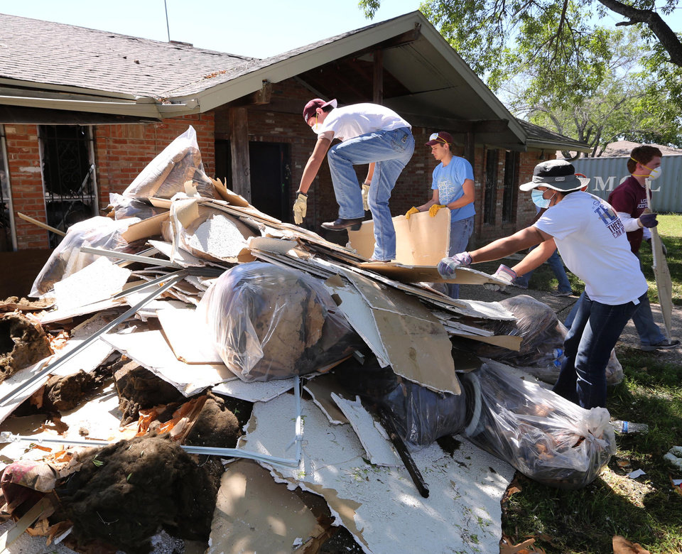 Photo - Texas A&M  students clean debris at a home in West, Texas, Saturday, May 4, 2013, that was damaged due to the explosion at a fertilizer plant in West on April 17. The plant that exploded, killing 14 people, injuring more than 200 others and causing tens of millions of dollars in damage to the surrounding area, had only $1 million in liability coverage, lawyers said Saturday. (AP Photo/Waco Tribune Herald, Rod Aydelotte)