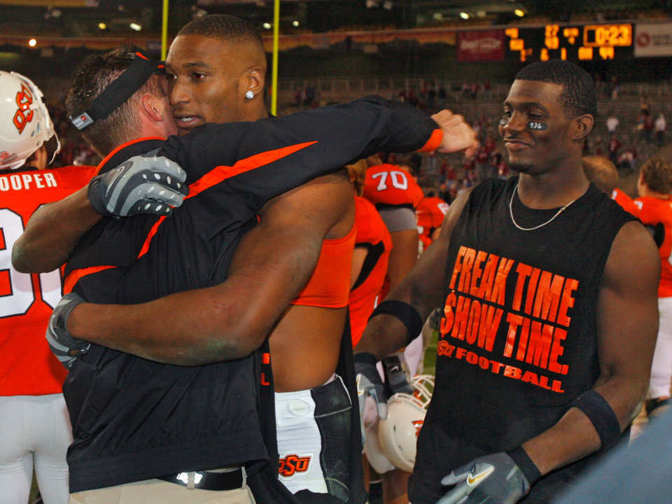 Photo - Oklahoma State's Adarius Bowman hugs coach Mike Gunday after the Cowboys' win in the Insight Bowl college football game between Oklahoma State University (OSU) and the Indiana University Hoosiers (IU) at Sun Devil Stadium on Monday, Dec. 31, 2007, in Tempe, Ariz. 