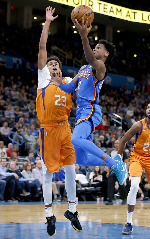 Photo - Oklahoma City's Shai Gilgeous-Alexander (2) goes up for a lay up as Phoenix's Cameron Johnson (23) defends during the NBA basketball game between the Oklahoma City Thunder and the Phoenix Suns at the Chesapeake Energy Arena in Oklahoma City , Friday, Dec. 20, 2019.   [Sarah Phipps/The Oklahoman]