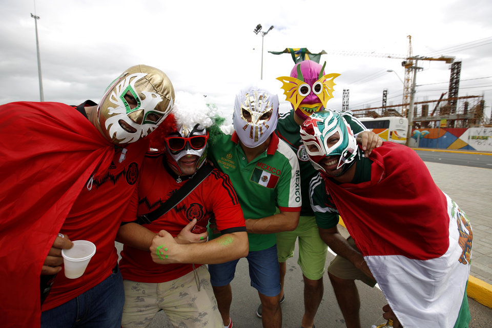 Photo - Mexican fans wearing wrestling masks pose outside of the Arena Castelao before the group A World Cup soccer match between Brazil and Mexico  in Fortaleza, Brazil, Tuesday, June 17, 2014. When Mexico tied Brazil 0-0, the number of fans wearing green or red in Castelao Stadium was nothing to sneeze at considering the World Cup host's hometown advantage. (AP Photo/Eduardo Verdugo)