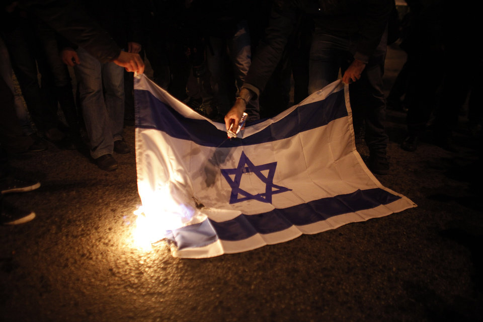 Photo -   Protesters burn an Israeli flag during a protest against Israel's bombardment of the Gaza Strip, in front of the Israeli embassy in Athens Saturday, Nov. 17, 2012. Several thousand marchers are commemorating the 39th anniversary of a deadly student uprising against the then ruling dictatorship, with more than 6,000 police deployed in the center of the Greek capital. Protesters after marching to the U.S embassy continued to demontsrate outside the Israeli embassy against bombardment of the Gaza Strip. (AP Photo/Kostas Tsironis)