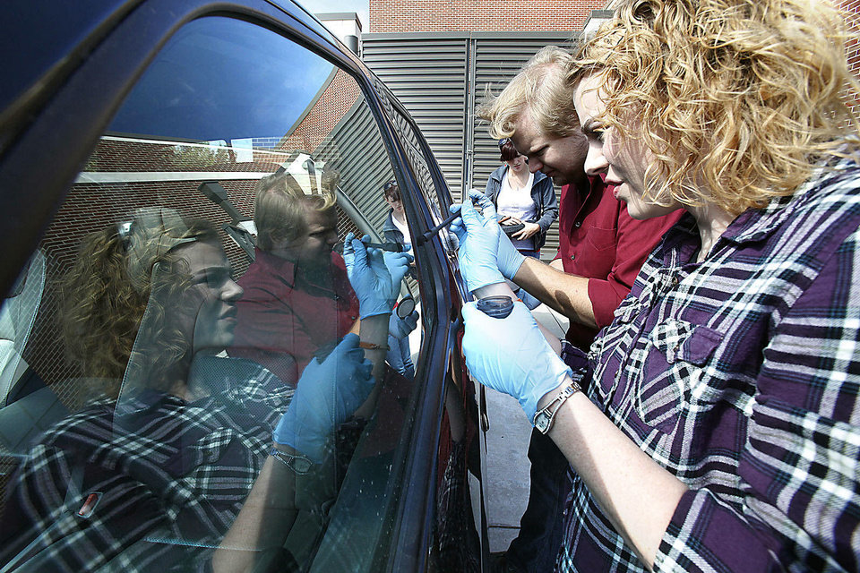 Above and left:  Students Christiana Burgess and Andrew Davisson dust  fingerprints at a simulated crime scene during a class on crime scene processing at the Forensic Science Institute on the campus of the University of Central Oklahoma. Photos by PAUL HELLSTERN, The Oklahoman