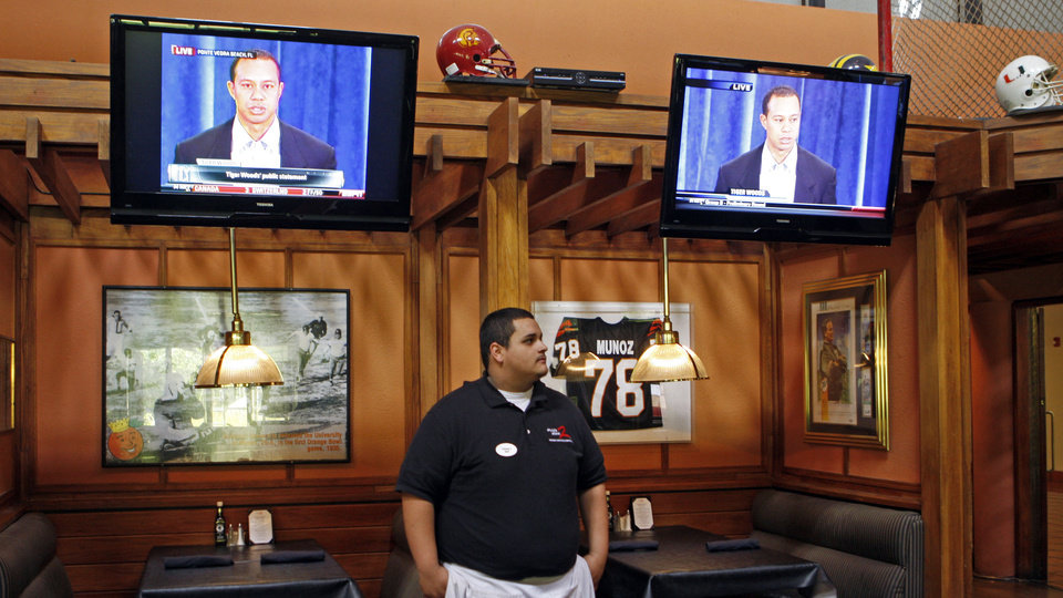 Photo - Yohanes Saenz, a busser at Shula's Steak restaurant, watches the Tiger Woods news conference in Miami Lakes, Fla., Friday, Feb. 19, 2010. (AP Photo/Alan Diaz) ORG XMIT: FLAD101