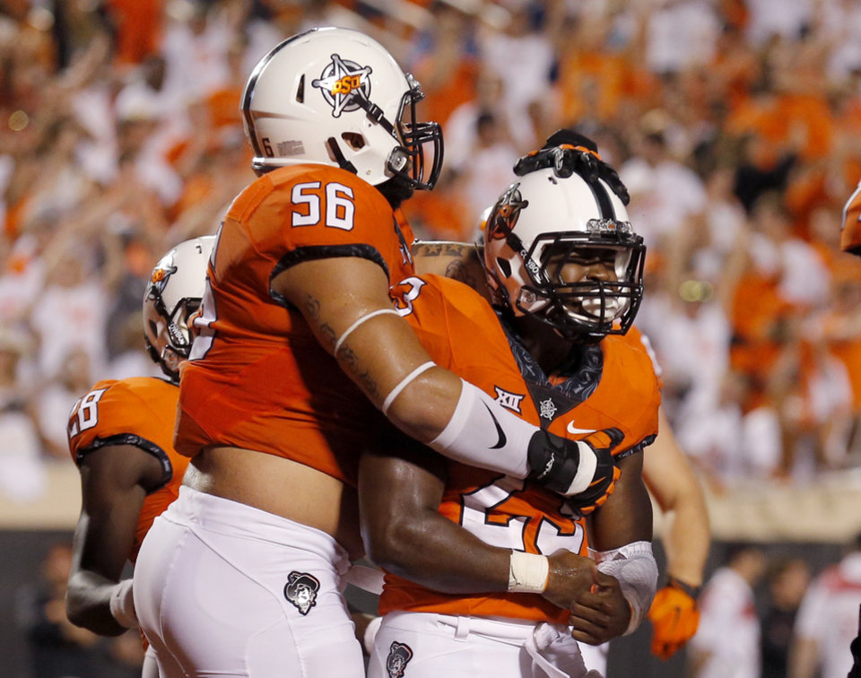 Photo - Oklahoma State's Rennie Childs (23) and Larry Williams (56) celebrate the Childs' game-winning touchdown during a college football game between the Oklahoma State Cowboys (OSU) and the Pitt Panthers at Boone Pickens Stadium in Stillwater, Okla., Saturday, Sept. 17, 2016. Photo by Sarah Phipps, The Oklahoman