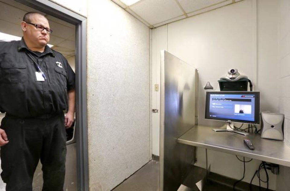Photo -  Oklahoma County Sheriff's Department Lt. Brad Logan stands in the doorway of the small room where a camera and video monitor were recently installed near the booking area at the Oklahoma County jail. The room and video system will eventually be used for preliminary and other court hearings. Operational since August, courts have yet to make use of it. [Photo by Jim Beckel, The Oklahoman]