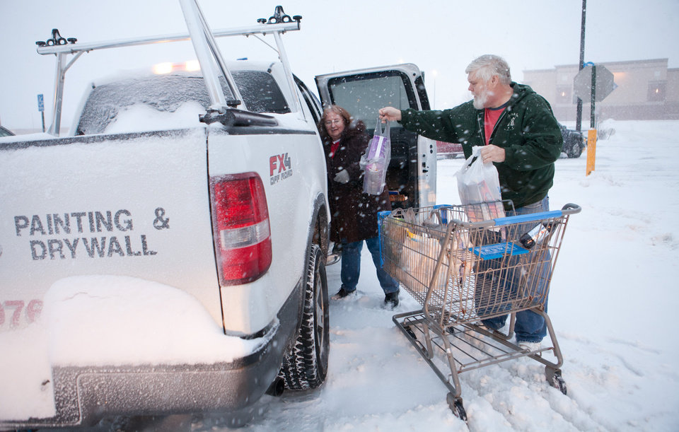 Photo - Dave and Debbie Teed load their shopping bags into their vehicle at the Walmart parking lot near the North Belt Highway in St. Joseph, Mo., Tuesday, Feb. 4, 2014. A winter storm bore down on Missouri Tuesday, dumping enough snow to make roads treacherous and forcing the cancellation of dozens of flights and hundreds of schools.  (AP Photo/The St. Joseph News-Press, Sait Serkan Gurbuz)