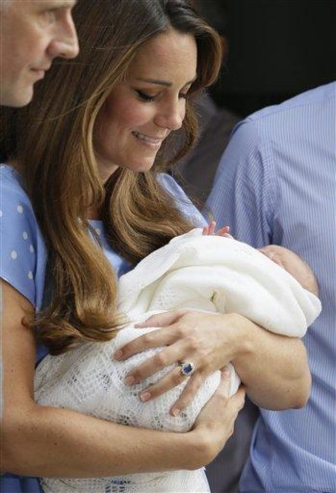 Photo - Kate, Duchess of Cambridge holds the Prince of Cambridge, as they pose for photographers outside St. Mary's Hospital exclusive Lindo Wing in London where the Duchess gave birth on Monday. Prince William, Kate and their baby left the hospital shortly after for London's Kensington Palace. (AP Photo/Alastair Grant)