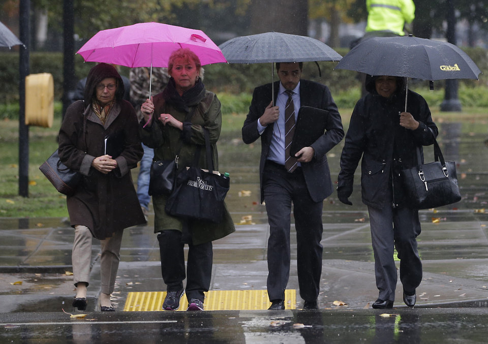 Photo - Umbrellas were in need as a storm passes through Sacramento, Calif., Thursday, Dec. 3, 2015. The first storm of December brought much needed rain to the valley and snow to the Sierra Nevada.(AP Photo/Rich Pedroncelli)