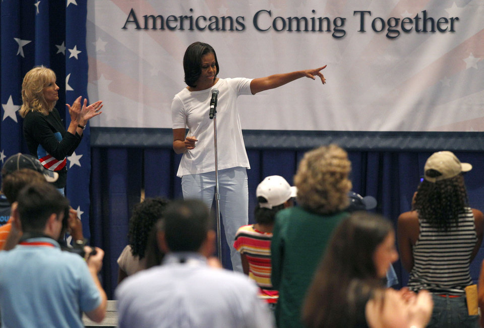 Photo -   First lady Michelle Obama, accompanied by Vice President Joe Biden's wife Jill Biden, left, speaks to volunteers at a USO service project during the Democratic National Convention in Charlotte, N.C., Thursday, Sept. 6, 2012. (AP Photo/Chuck Burton)