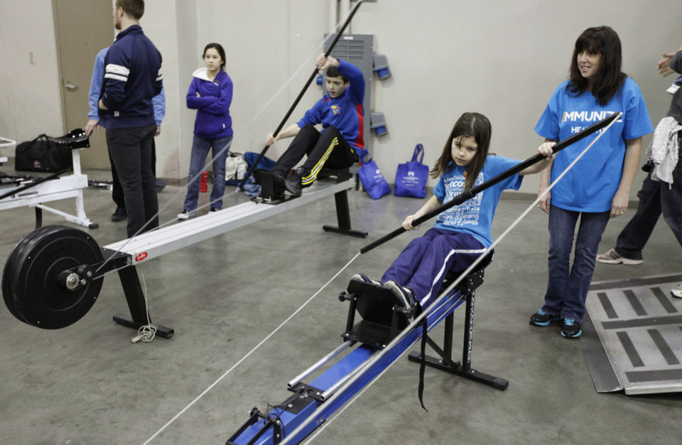 Photo - Children practice rowing during Bart & Nadia's Sports & Health Festival at the Cox Convention Center in Oklahoma City, OK, Saturday, February 16, 2013,  By Paul Hellstern, The Oklahoman