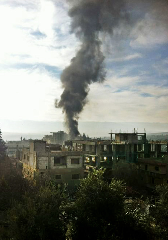 Photo - Black smoke rises from the site of a car bomb explosion, at a stronghold of Lebanon's militant Hezbollah group, in the center of the predominantly Shiite town of Hermel, northeast Lebanon, about 10 miles (16 kilometers) from the Syrian border, Thursday, Jan. 16, 2014. A car bomb struck a northeastern Lebanese town close to the Syrian border during rush hour on Thursday, killing and wounded several, security officials said. It was the latest in a wave of attacks to hit Lebanon in recent months as the civil war in Syria increasingly spills over into its smaller neighbor, attacks that have killed scores of people here and bitterly divided the Lebanese. (AP Photo)