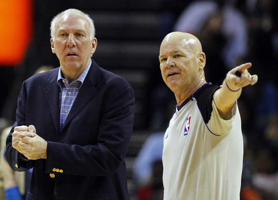 San Antonio Spurs head coach Gregg Popovich, left, talks with referee Joe Crawford, right, during the first half of an NBA basketball game against the Charlotte Bobcats in Charlotte, N.C., Saturday, Dec. 8, 2012. (AP Photo/Chuck Burton)