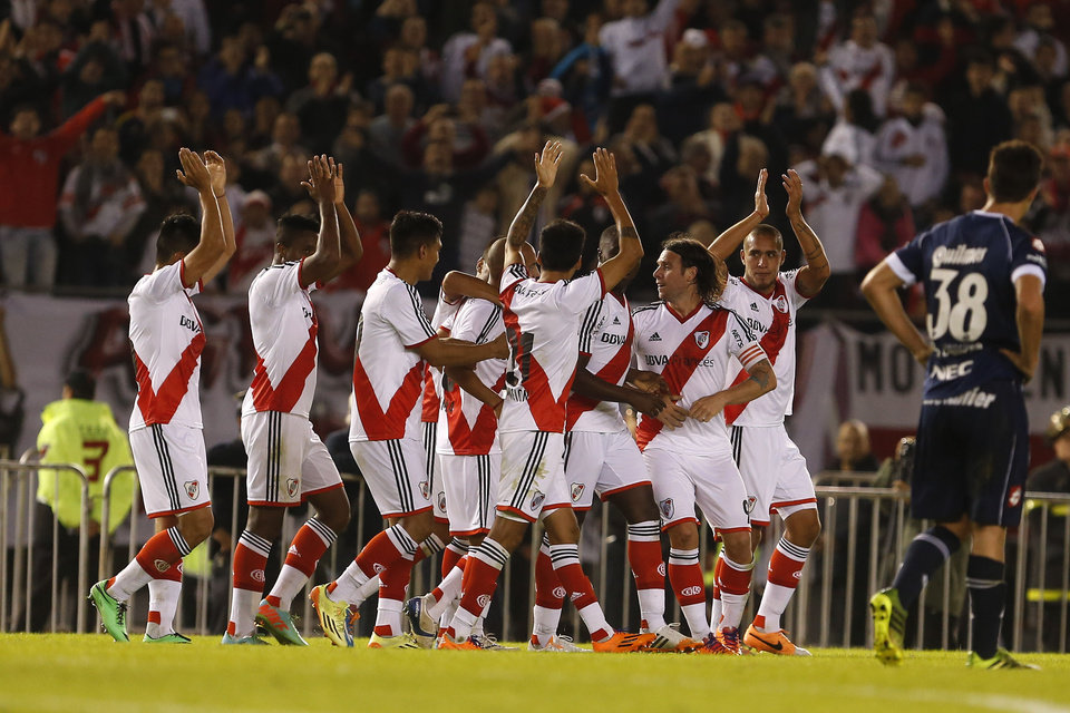 Photo - River Plate players, center, celebrate with teammate Cristian Ledesma, center, after he scored against Quilmes during an Argentine league soccer match in Buenos Aires, Argentina, Sunday, May 18, 2014. (AP Photo/Victor R. Caivano)